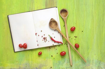 Vintage cookbook with empty pages for recipes, spices and wooden spoons, mock up with free copy space