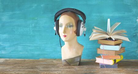 audio book concept with open book headphones and display dummy, mannequin, panoramic, good copy space