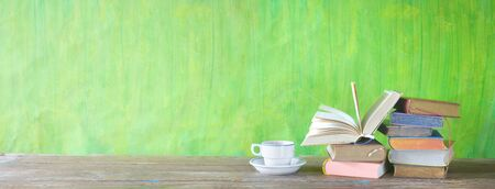 Open Book and stack of multicolored hardback books with a cup of coffee, reading education, literature, panoramic, good copy space Zdjęcie Seryjne