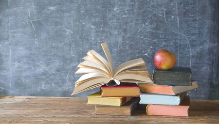 open book and stack of books with chalk board and red apple.Back to school, education, learn concept, free copy space