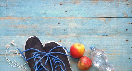 Fitness, sport, workout, running, concept with pair of runners, water, apple headphones. Free copy space, flat lay.