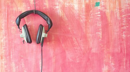 Vintage headphones hanging on grungy wall, listening,podcast, music concept