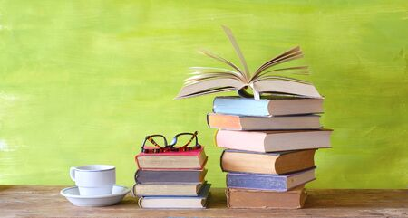 Open Book and a stack of multicolored hardback books with a cup of coffee, reading education, literature, good copy space Zdjęcie Seryjne