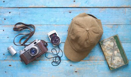 Old analog camera, light meter, film can, cap and notebook with pen, photography, vintage photo gear concept