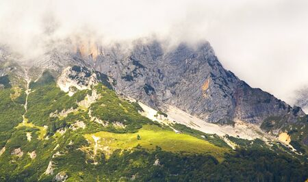 mountains in the alps with cloudy hillsides, alp and chalet