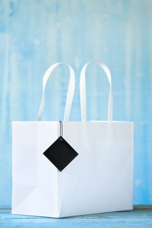 White empty paper shopping bag with blank hang tag. Sale, buying, shopping mock up with free copy sapce