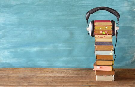 audio book concept with large stack of books and headphones, good copy space Stock Photo