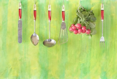a bunch of fresh radish and hanging vintage kitchen utensils , helathy eating,vegetarian,cooking concept, free copy space