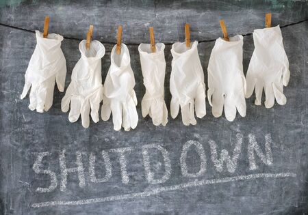 Health care system shutdown symbol picture, medical gloves and black board, coid-19.corona virus