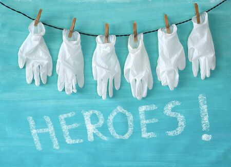 "Giving respect to the health care system, symbol picture,medical gloves and the message ""Heroes"",covid-19, corona virus"