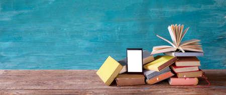 Stack of books and an e-book reader. E-book, book fair, reading, realaxing, education concept. Free copy space on the screen of the e-book reader. Reklamní fotografie