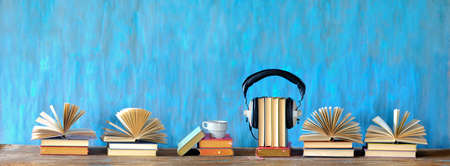 audio book concept with open books, cup of coffee, and vintage headphones, panoramic, good copy space Zdjęcie Seryjne