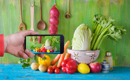 taking a shot with smartphone of organic food ingredients, vegetables, kitchen utensils, posting on social media, healthy eating concept Zdjęcie Seryjne