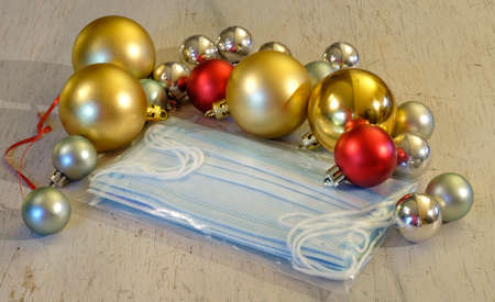 Christmas in times of Covid-19, surgical face masks and christmas balls, symbolic picture