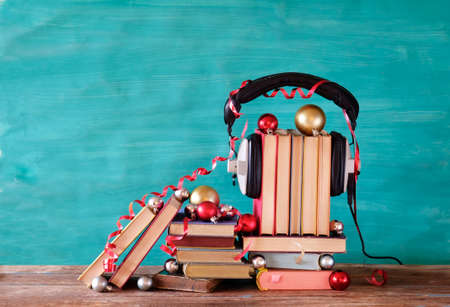 audio books as christmas gift, present with christmas decoration, headphones and pieces of books, reading, literature, education, free copy space Zdjęcie Seryjne