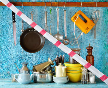 gastronomy corona lockdown, restaurant kitchen utensils with warning tape, symbolic picture