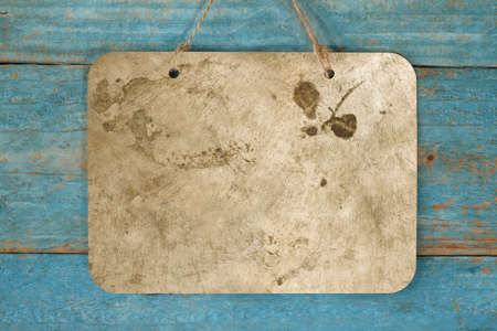 blank grungy metal sign hanging on blue wooden planks wall, free copy space
