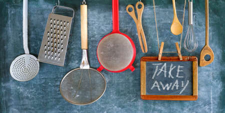 kitchen utensils and message on black board,take away food concept