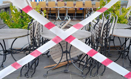 Gastronomy lockdown due to epidemic, closed restaurant terrace,chairs,tables and barrier tape, symbolic