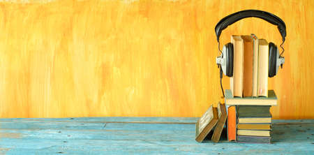 audio book concept with stacks of books and vintage headphones,literature,entertainment,education, good copy space