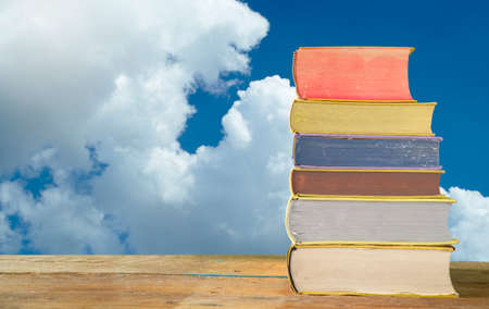 stack of books with beautiful clouds in the background free copy space, summer holidays relaxing concept