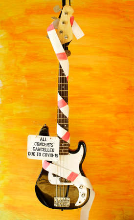 cancellation of concerts due corona virus lockdown,bass guitar,warning tape and cancellation sign, symbol picture