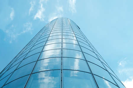 Facade of modern skyscraper with reflection of cloudy sky, low angle shot, free copy space Standard-Bild