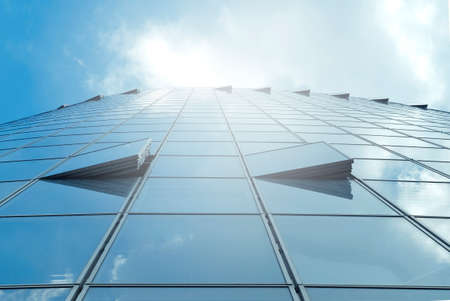 Facade of modern skyscraper with reflection of cloudy sky and sunbeams, low angle shot, free copy space Standard-Bild
