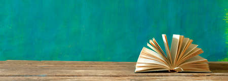 open book on green background. Reading,literature,education,library,home office, back to school concept,panoramic, large free copy space