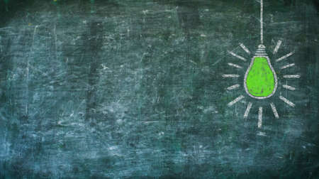 renewable energy and power concept,green lightbulb on black board, design template, large copy space