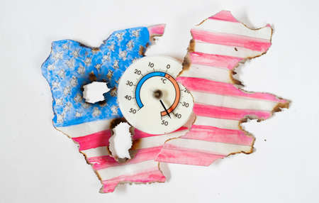 Heat wave in north america,burned USA flag and thermometer displaying high temperature, climate change concept
