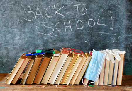 Back to school concept,school supplies and COVID 19 prevention items on classroom desk with books,eyeglasses,pens on chalkboard with back to school caption Standard-Bild