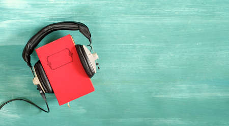 audio book concept with book and vintage headphones,literature,entertainment,education,copy space on the book cover