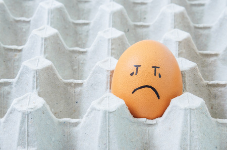 arranged: brown eggs face crying arranged in carton Stock Photo