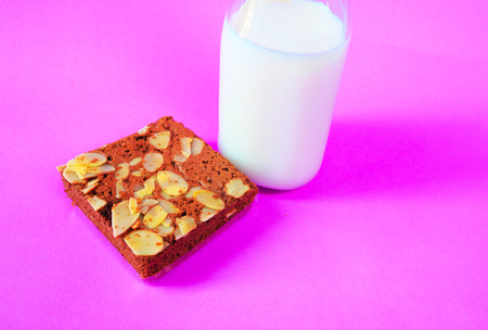 plato del buen comer: Brownies de chocolate con la botella de leche sobre fondo morado Foto de archivo