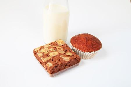 plato del buen comer: Brownies de chocolate y pastel de pl�tano con leche en el fondo blanco Foto de archivo