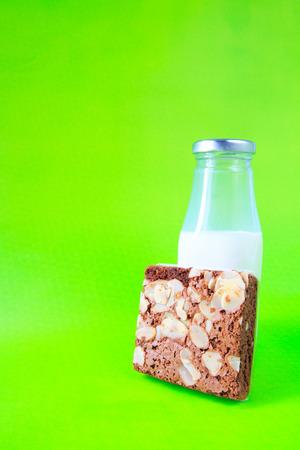 plato del buen comer: Brownies de chocolate con la botella de leche sobre fondo verde Foto de archivo