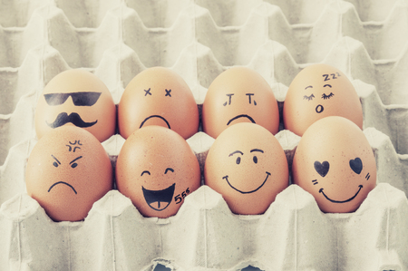 small group of objects: eight brown eggs  with faces drawn  arranged in carton Stock Photo