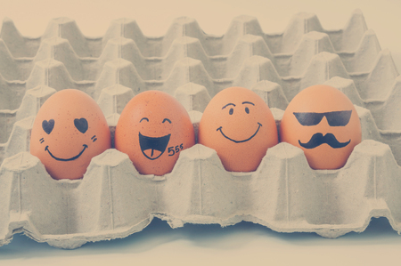 teamwork cartoon: four brown eggs  with faces drawn  arranged in carton