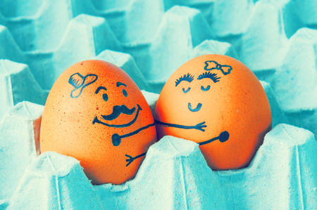 medium group of objects: Two eggs hugging  arranged in carton Stock Photo
