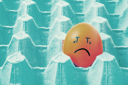 emote: brown eggs face crying arranged in carton Stock Photo