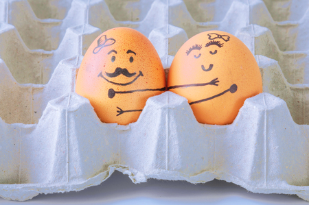 breakfast smiley face: Two  eggs hugging  couple in empty carton