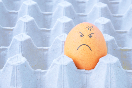 face to face: Angry face Eggs in brown paper box