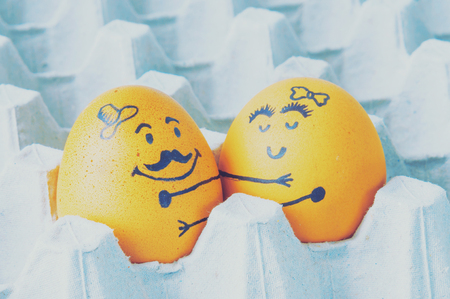 breakfast smiley face: Two eggs hugging  arranged in carton Stock Photo