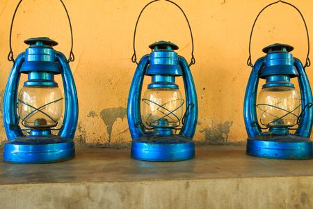 kerosene: vintage kerosene oil lantern lamp burning on vintage yellow wall