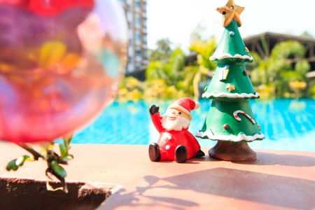 standalone: santa doll with christmas tree ,pool background