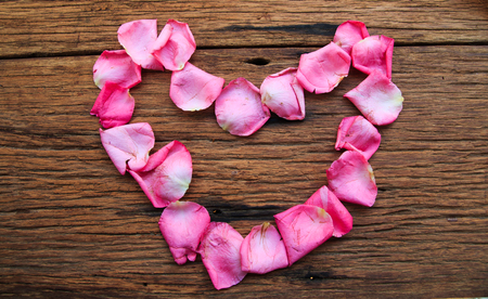 pink rose petals: Beautiful heart of pink rose petals isolated on old wood