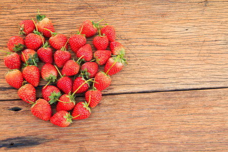 wood table: Red Strawberries with heart shape on wood table