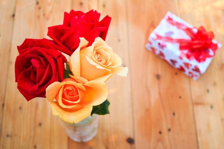 rosas naranjas: Rosas rojas y flores de color naranja en la mesa de madera Foto de archivo