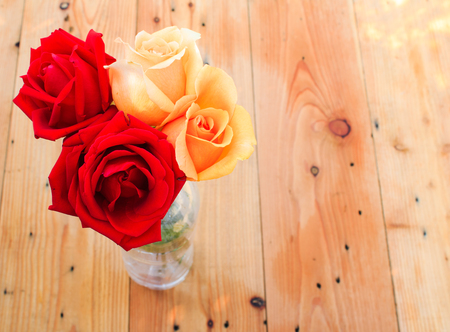 rosas naranjas: Red and orange roses flowers on wood table Foto de archivo